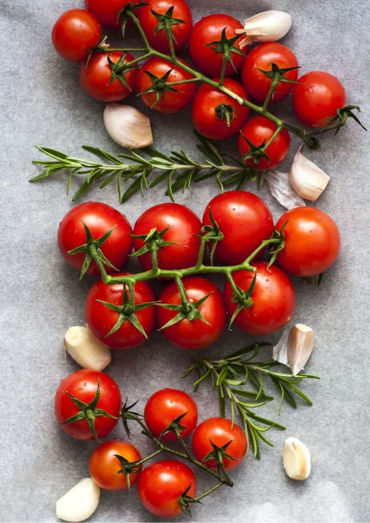 truss tomatoes and garlic on a baking tray