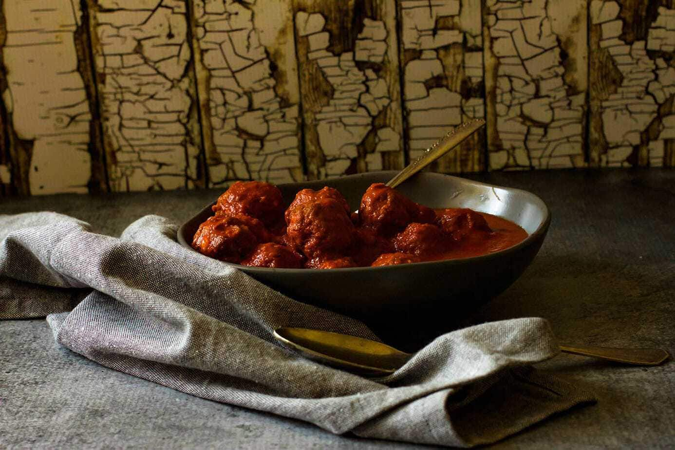 Lamb meatballs in bowl with tomato sauce