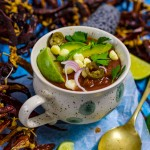 Chicken taco soup bowl with dried chillies, avocado and lime
