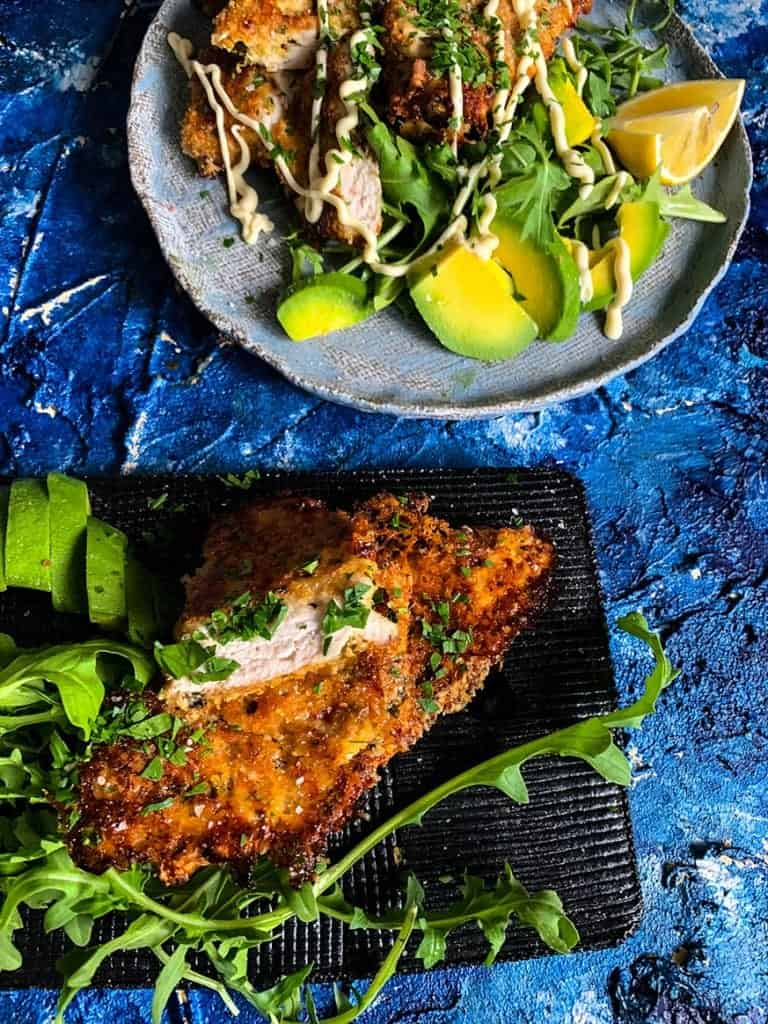 Chicken Milanese on black plate with rocket