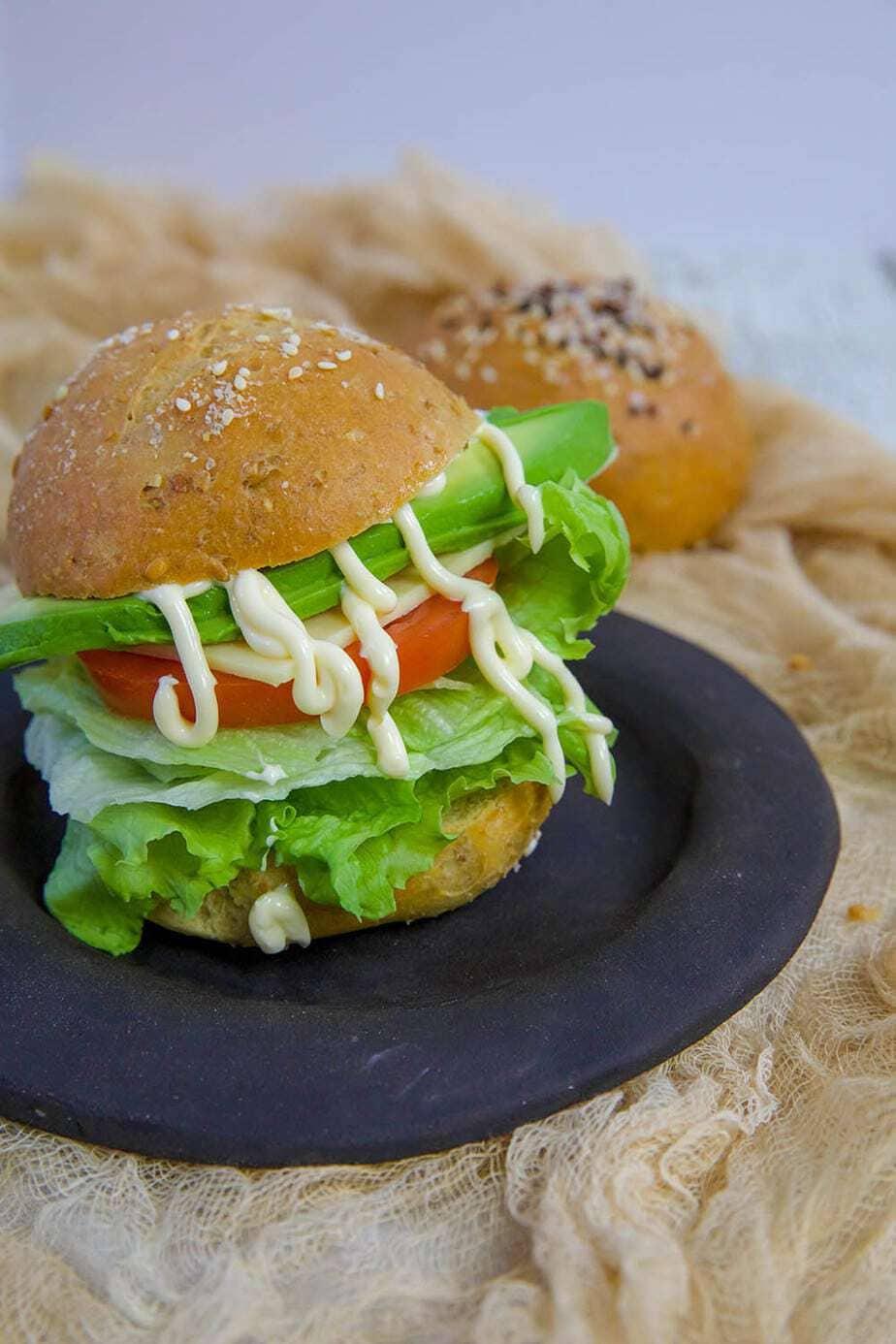 Bun with mayo and salad on a plate