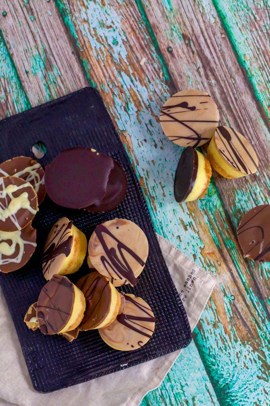 keto chocolate caramel tarts on black tray and green wood background
