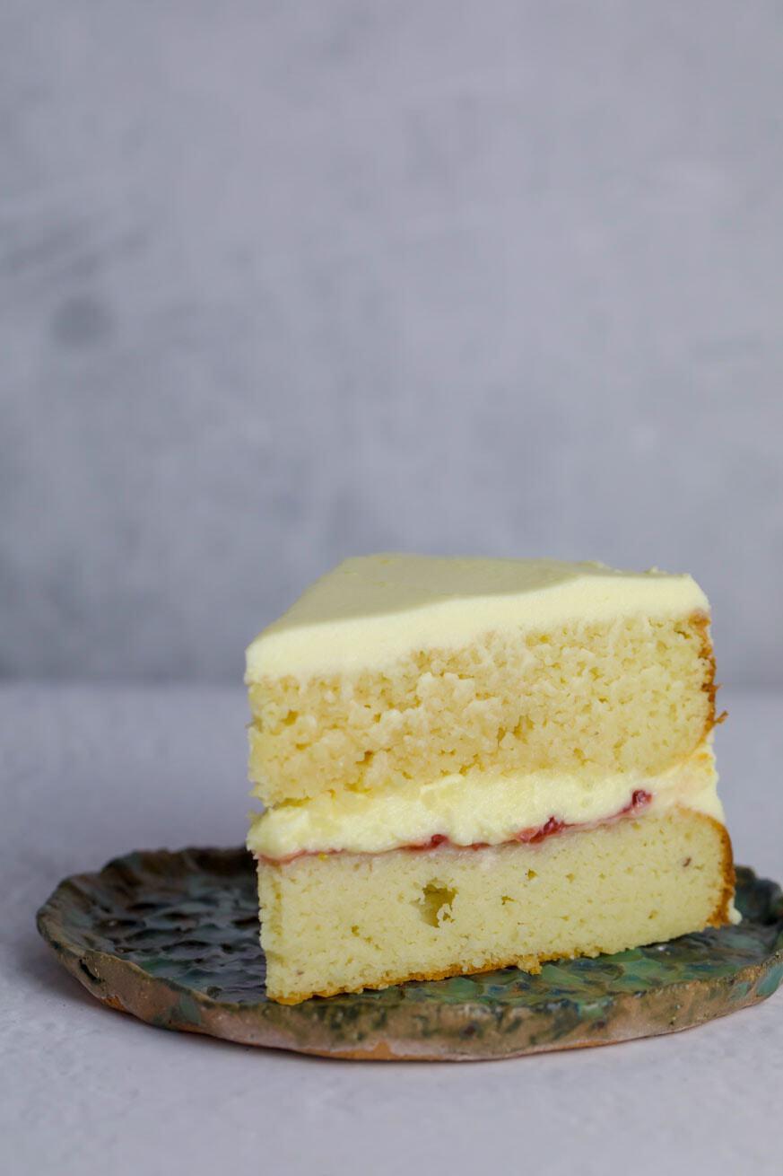 Slice of keto vanilla cake on a green plate