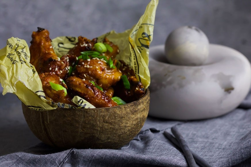 Keto Crispy Chicken Wings in a coconut bowl on grey cloth