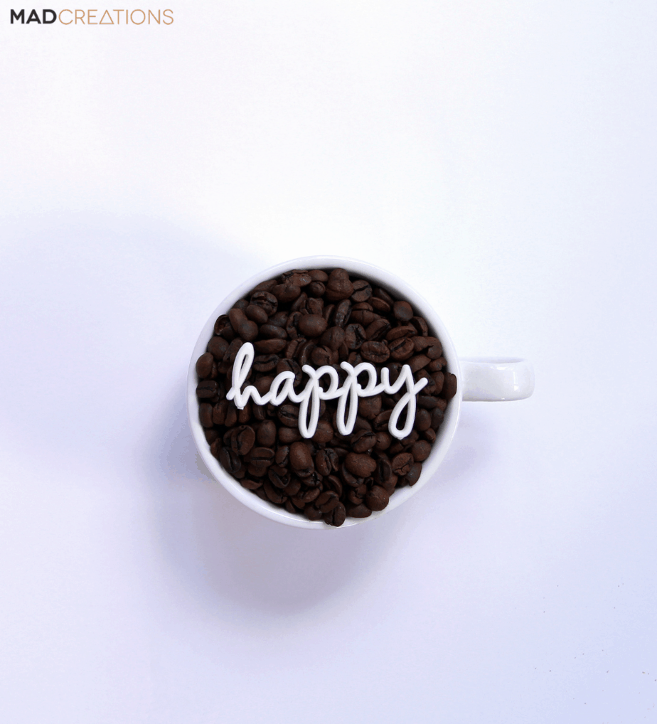 cup of coffee beans with happy written on top
