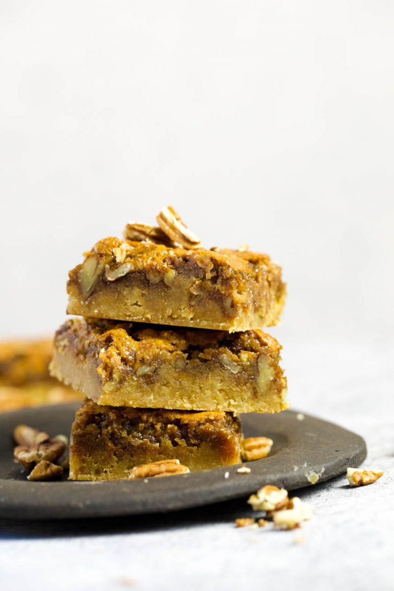 Pecan Pie Bars on a black plate on a white background