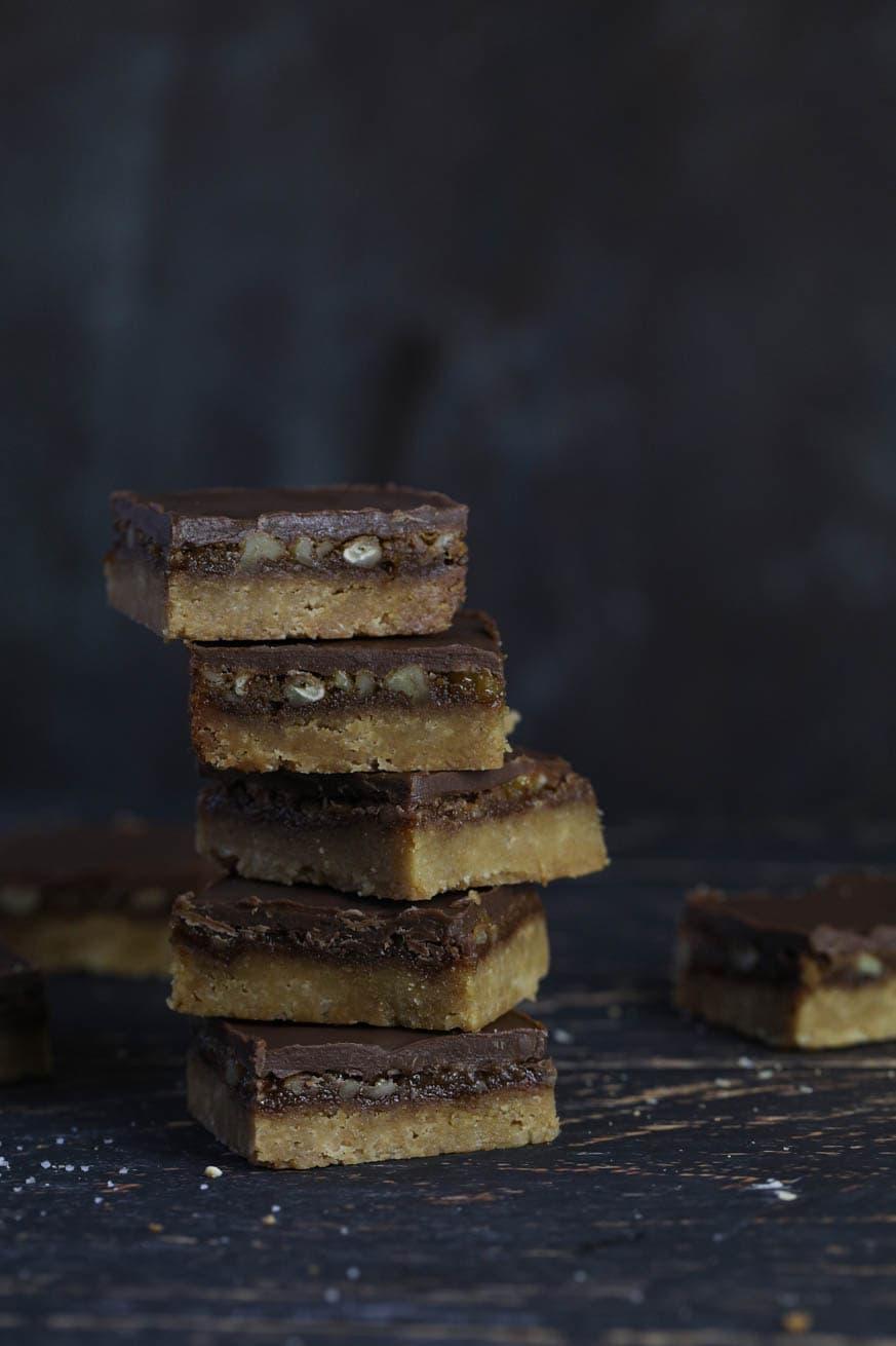 Chocolate pecan bars piled up on dark background