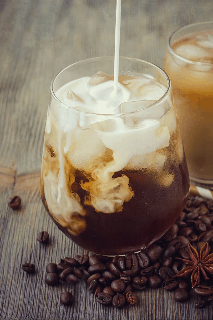 Milk pouring into cold coffee
