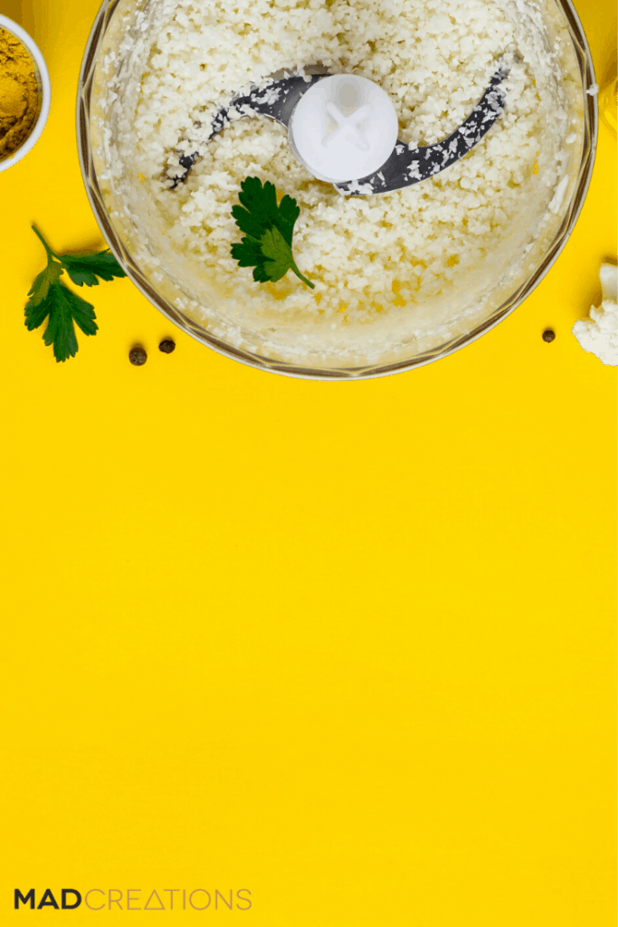 cauliflower rice in a food processor on a yellow background