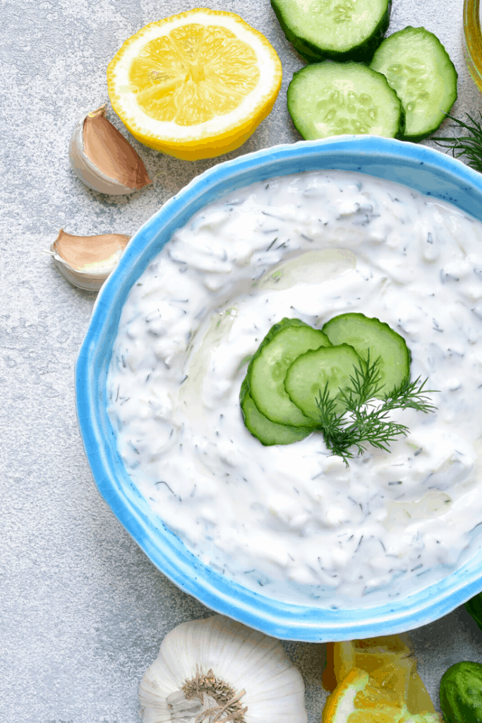 Raita in a blue bowl with lemon and cucumber