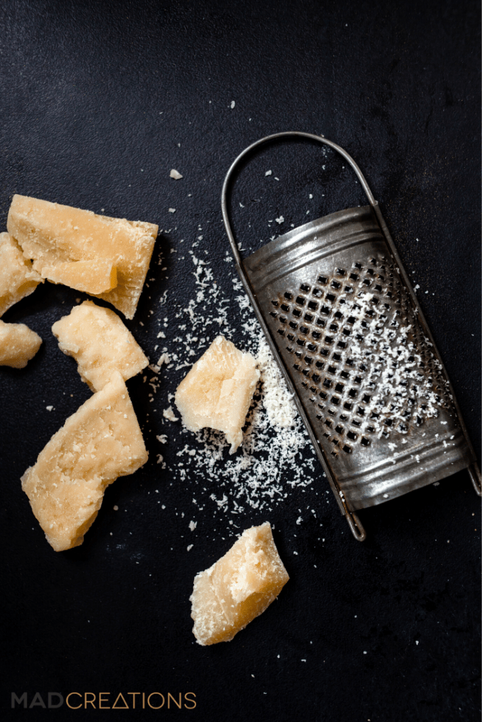 parmesan and grater on black background