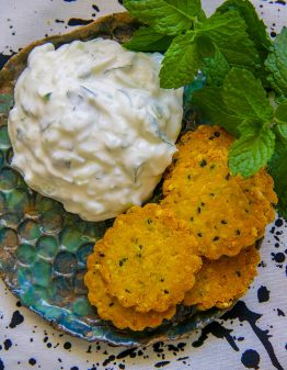crackers and raita on a green plate