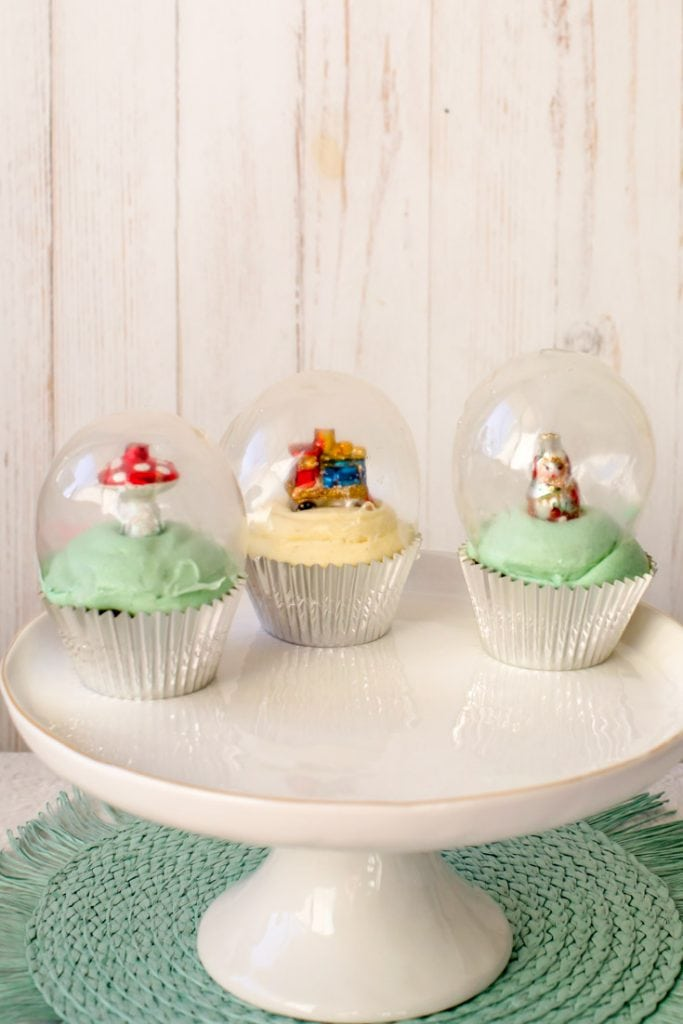 3 snowglobe cupcakes on a white cake stand
