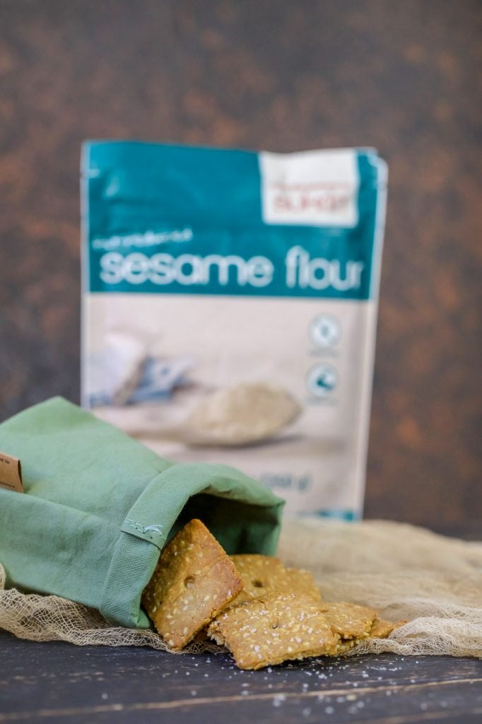 Sesame crackers in a green canvas bag and a bag os sesame flour