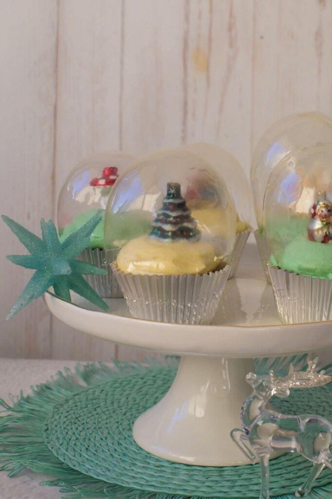 Snow globe cupcakes on a white cake platter