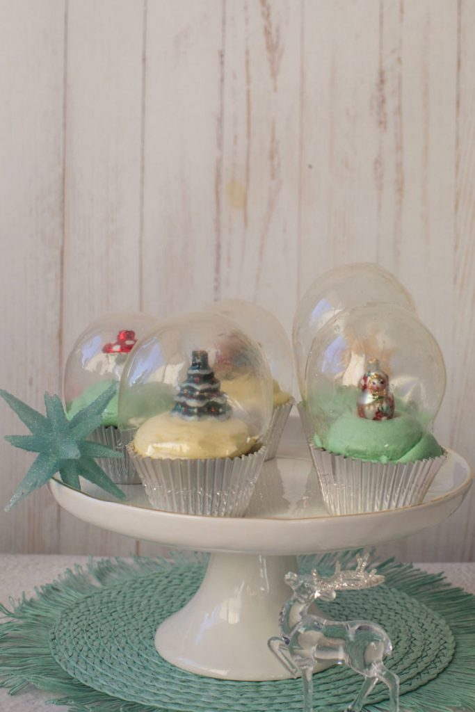 snow globe cupcakes on a white cake stand