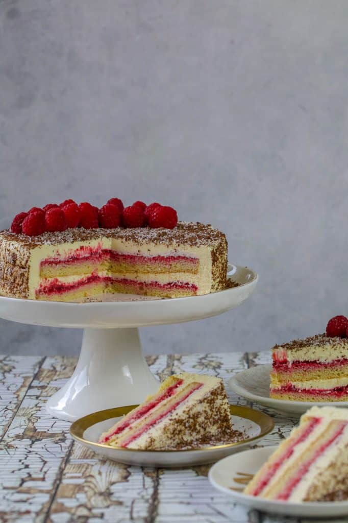 Chocolate coated cheesecake with raspberries on white cake stand