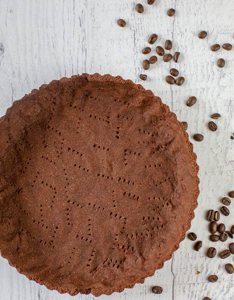 A close up of a chocolate pie crust on white wood