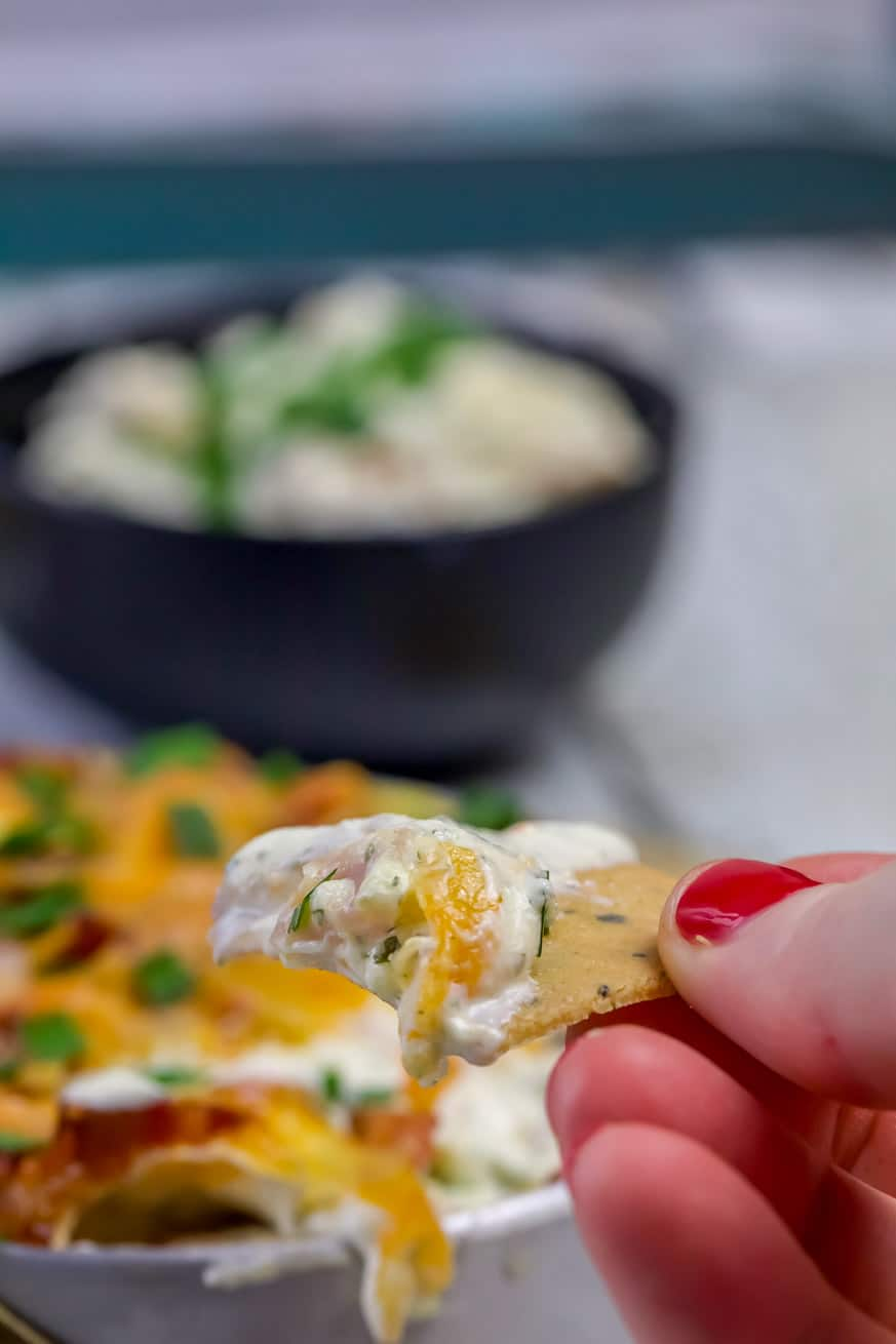 keto cheese crackers with cheesy dip in a small saucepan on white wood table