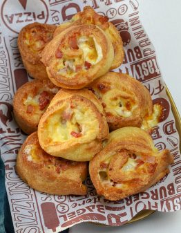 cheese and bacon scrolls on white and brown newspaper