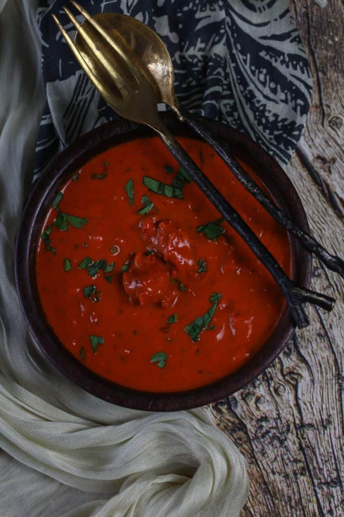 a bowl of butter chicken on a wood backdrop