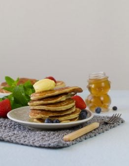stack of pancakes on a white plate with berries and fruit