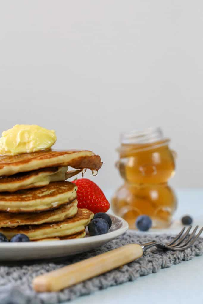 stack of pikelets with syrup and berries