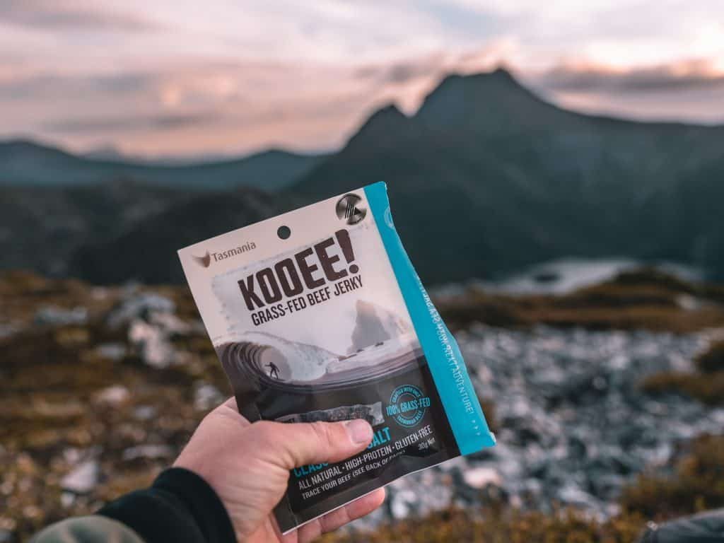 Kooee jerky in a hand with landscape background