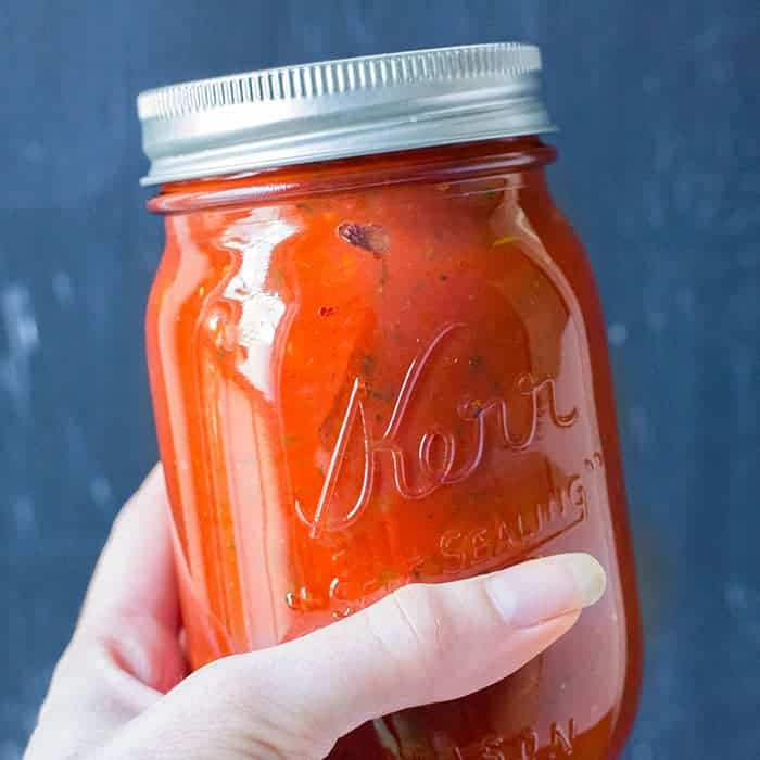 jar of tomato sauce in a hand