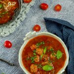Bowl of minestrone soup on a grey table with tomatoes and herbs around it