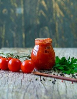 Keto Marinara Pizza Sauce in a jar with tomatoes and parsley