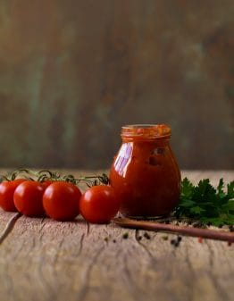 tomatoes, herbs, pepper and a jar of sauce on a wood table