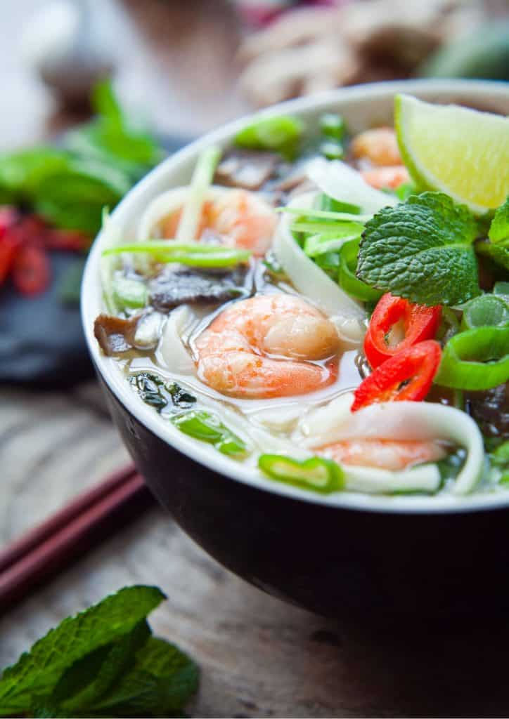 noodle soup with shrimp and fresh herbs in a bowl