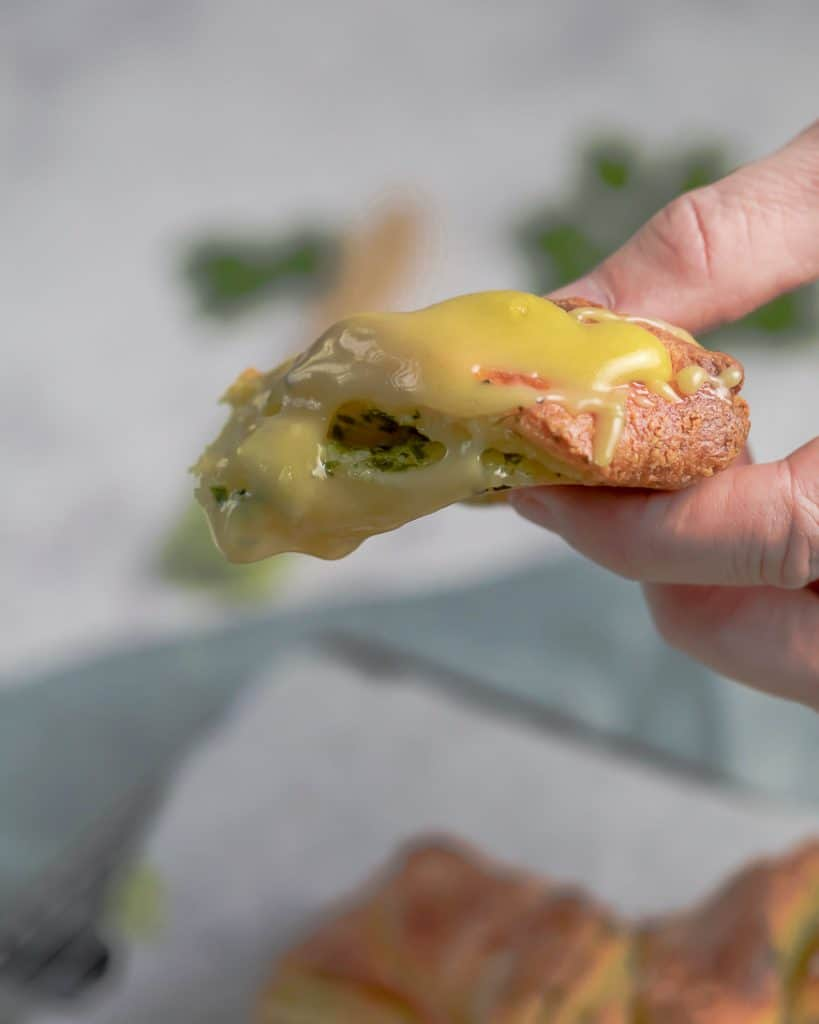 piece of bread in a hand covered in cheese