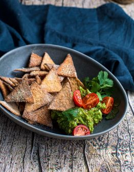 bowl of keto corn chips with guacamole and tomato