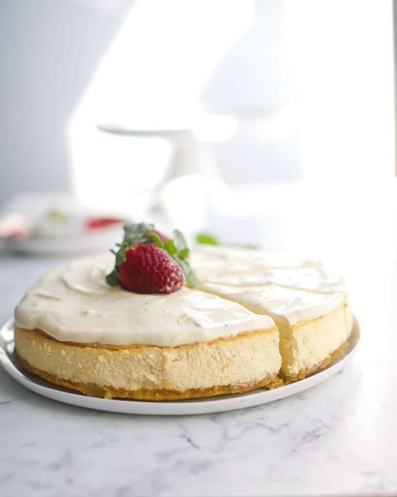 cheesecake on a white marble countertop with a strawberry on top