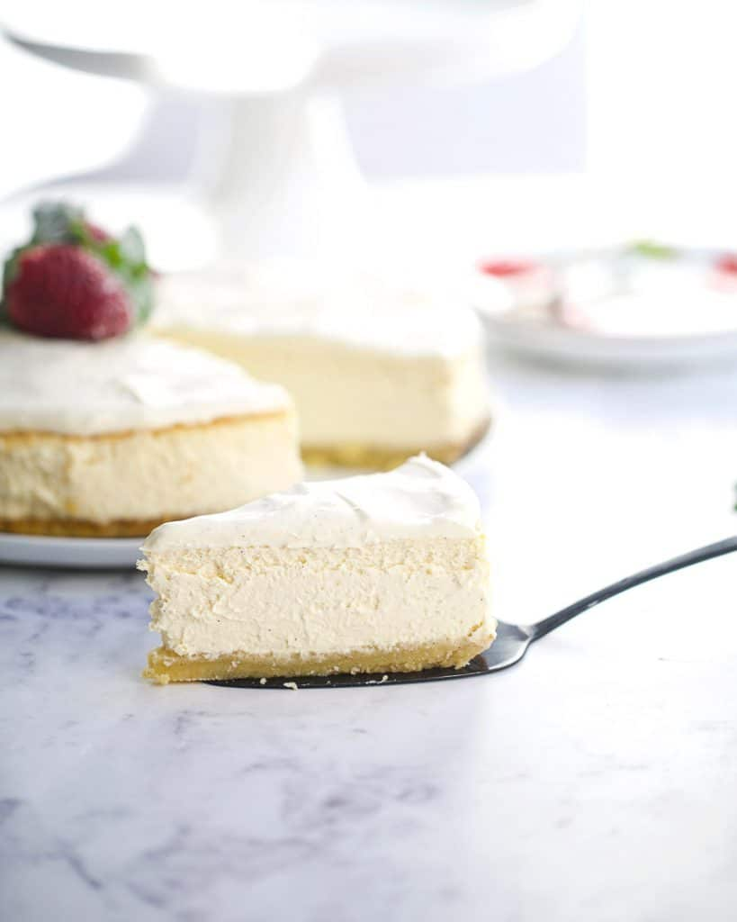 Slice of cheesecake in front of the whole cheesecake