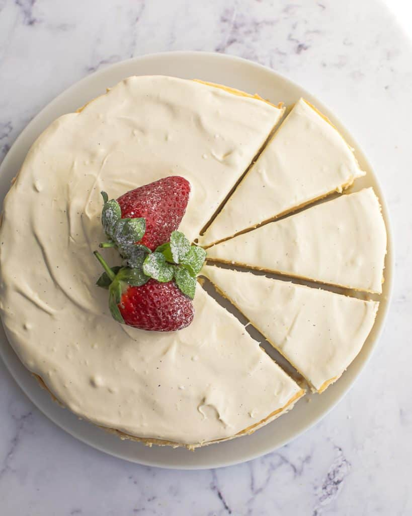 overhead shot of a cheesecake with 3 slices cut on a white plate