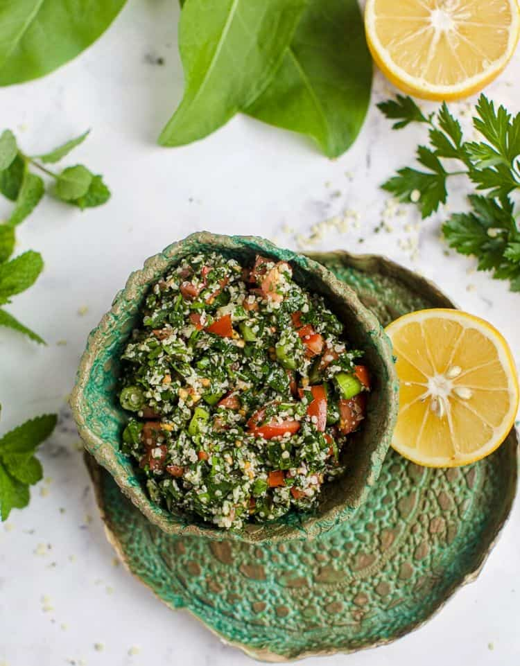Keto Tabbouleh Salad in a green bowl with fresh herbs and lemon around it