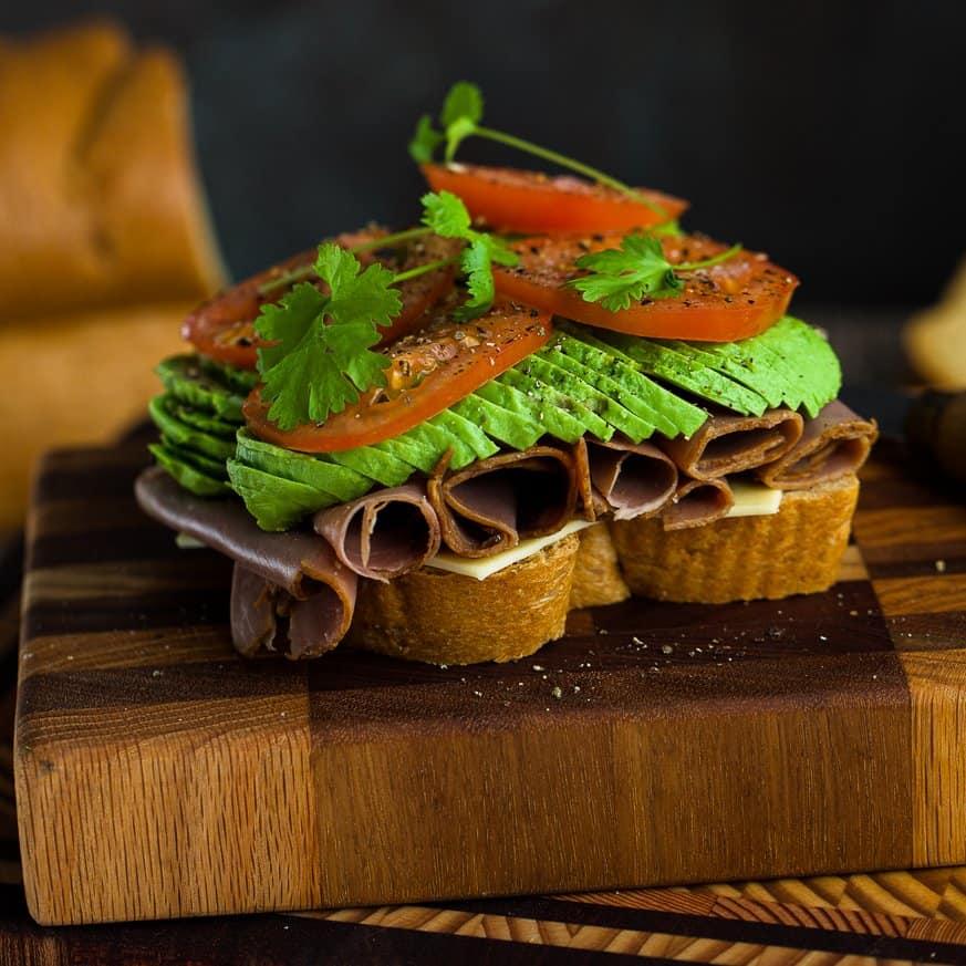 A roast beef sandwich on a cutting board