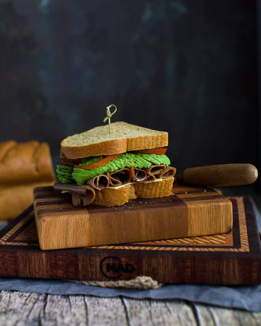 A sandwich with beef and avocado on a cutting board