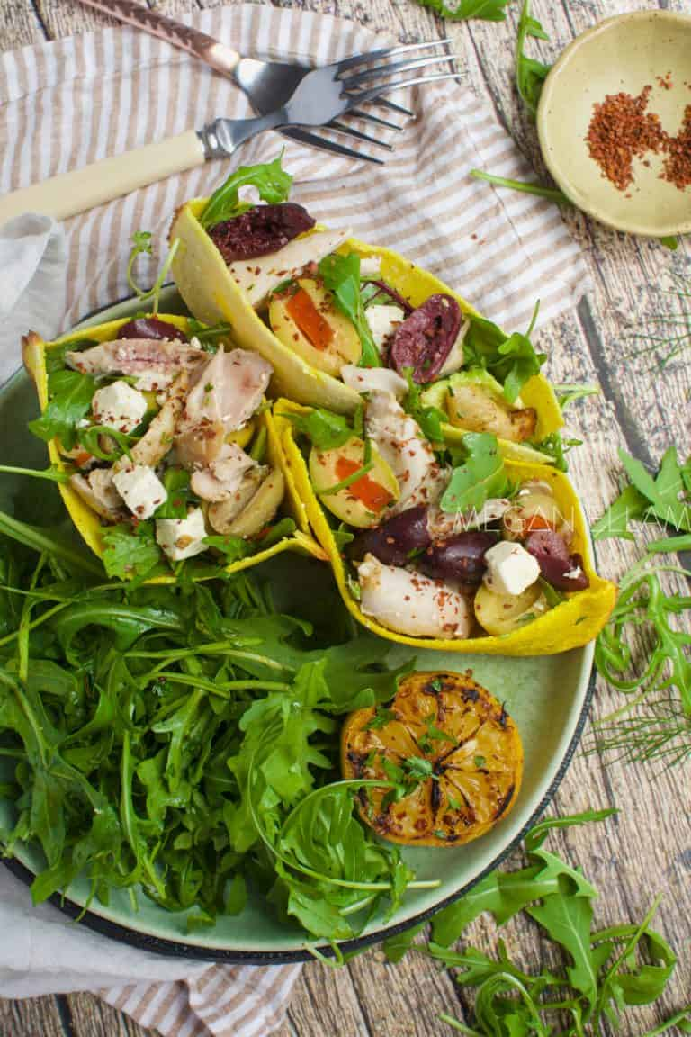 keto pita bread pockets filled with salad on a plate with leafy greens