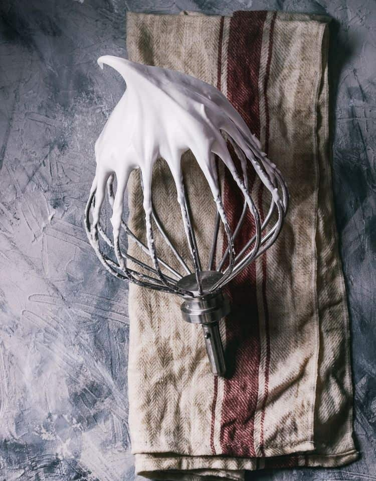 a cake beater covered in raw meringue mixture