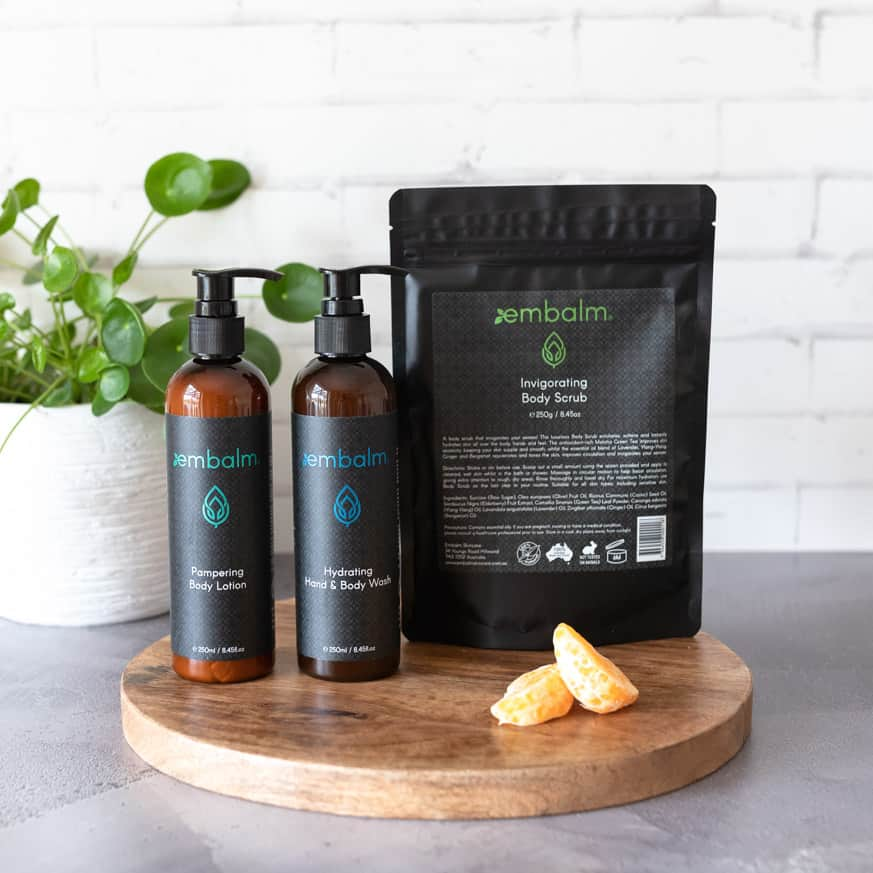 two bottles of skin care and body scrub on a bench with a plant