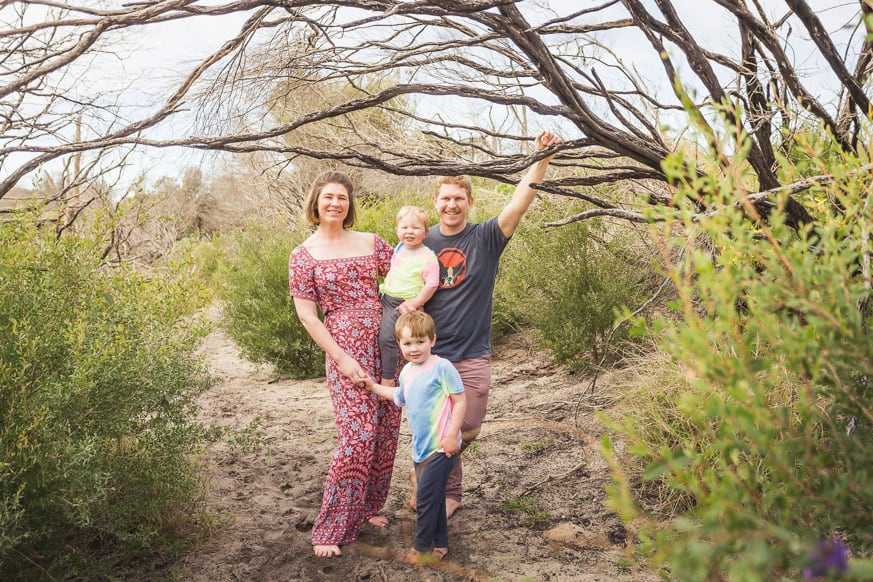 a man and woman and their two sons near a tree