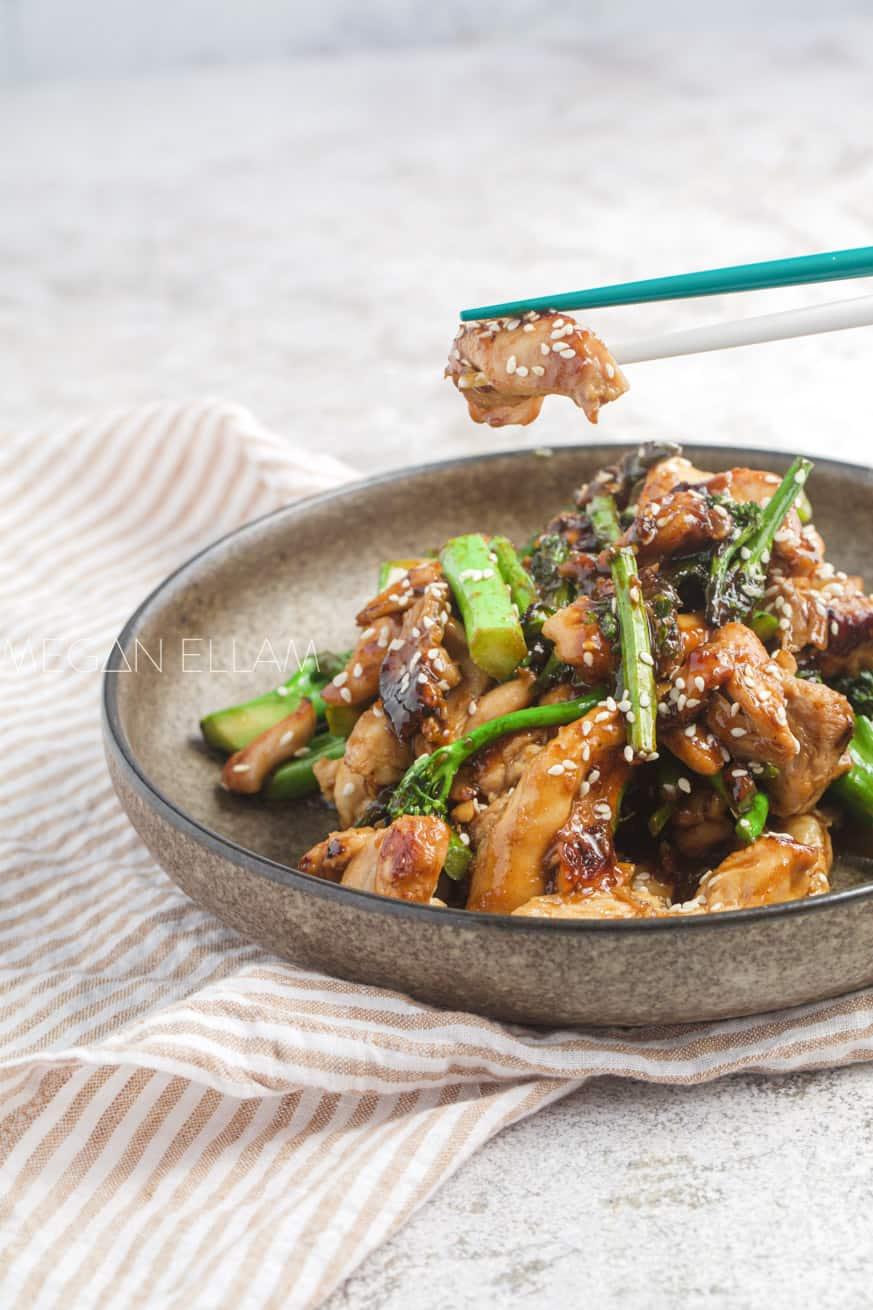 chicken in chopsticks above a bowl