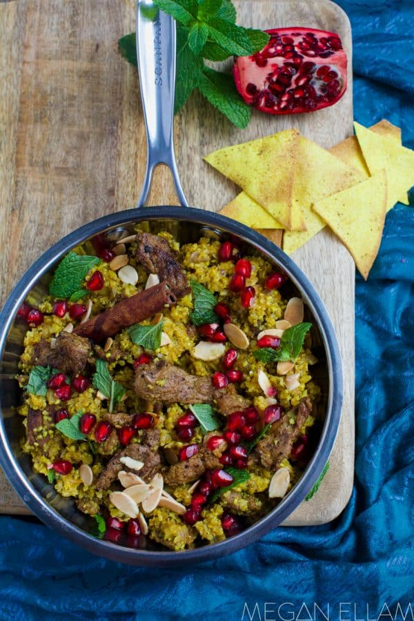 lamb and pomegranate seeds in a frying pan