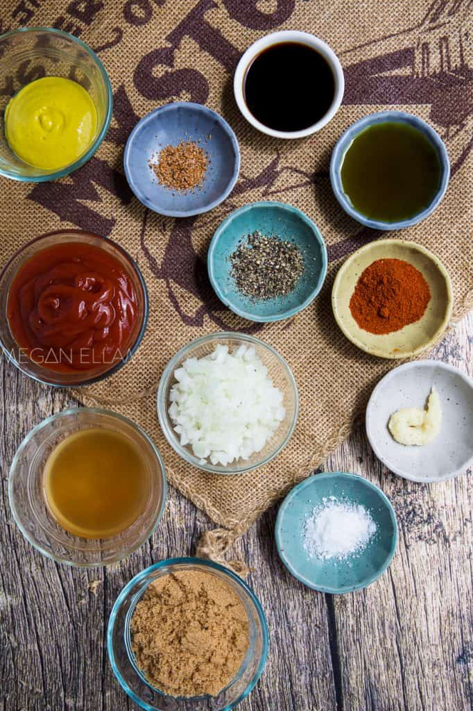 14 bowls of spices and sauces on a wood background