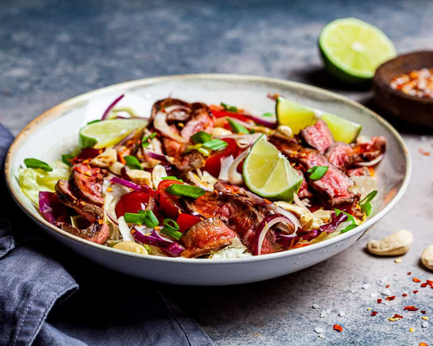 Asian beef salad on a speckled brown background