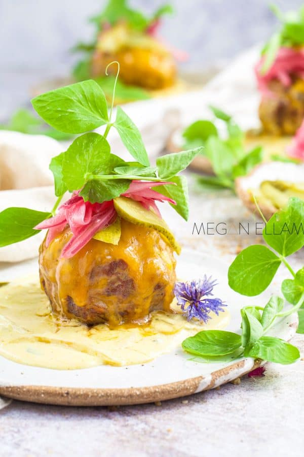 a meatball with cheese and salad on top.